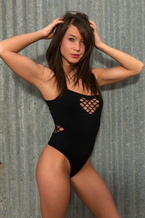 Pretty petite brunette in a black bodysuit Stock Photo