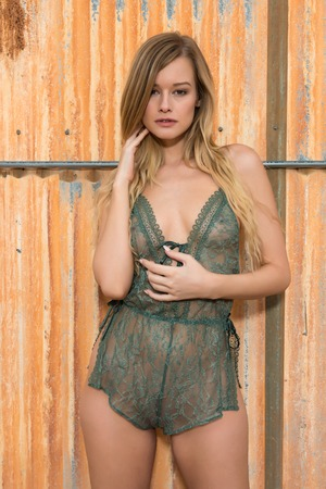Beautiful slender blonde in a forest green bodysuit Stock Photo