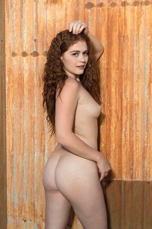Petite young redhead standing nude against a rusty wall Stock fotó