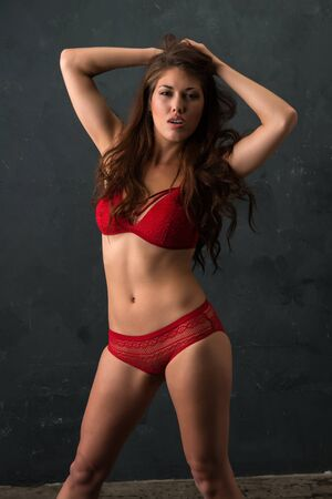 Beautiful petite brunette dressed in red lingerie Stock Photo