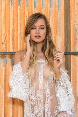 Schöne schlanke Blondine nackt unter einer weißen Netzstrickerei Standard-Bild - 78520837