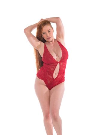 Curvy giovane rossa in un abito di pizzo rosso Archivio Fotografico - 80767044