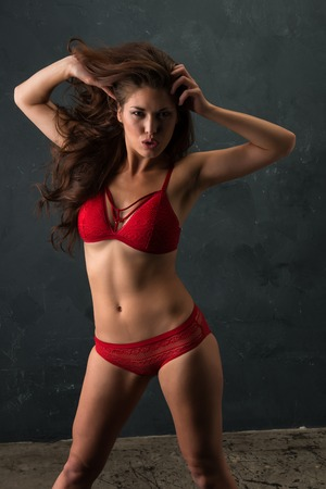 Beautiful petite brunette dressed in red lingerie Banco de Imagens