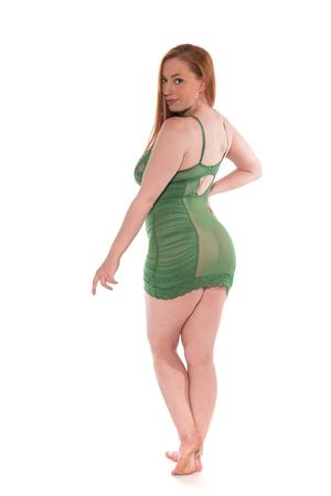 Pelirroja joven curvy en un chemise verde del cordón Foto de archivo - 80617635