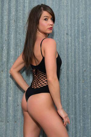 Pretty petite brunette in a black bodysuit Stock Photo