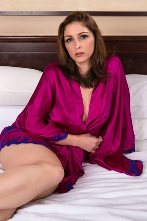 Beautiful brunette nude under a purple robe Stock Photo