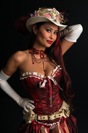 Beautiful mature redhead dressed in a sexy steampunk outfit Фото со стока