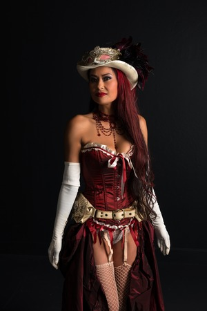 Beautiful mature redhead dressed in a sexy steampunk outfit Stock Photo