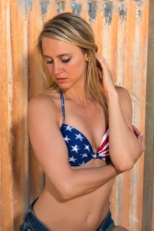 Beautiful slender tanned blonde in Stars & Stripes bikini top and cutoff jeans Stock Photo