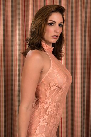 Beautiful brunette in a sheer peach bodysuit Stock Photo