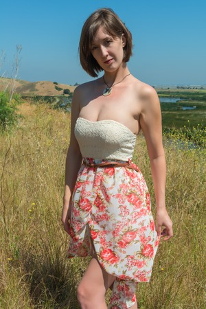 Statuesque young brunette in a strapless top and flower print skirt Stock Photo
