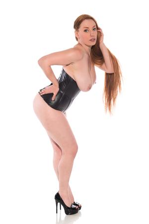 Pelirroja joven curvy en un cincher negro de la cintura Foto de archivo - 84048330