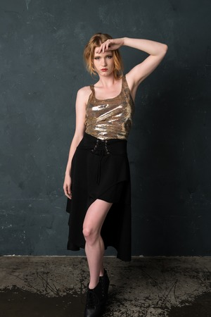 Pretty strawberry blonde woman in a sequined blouse and black skirt