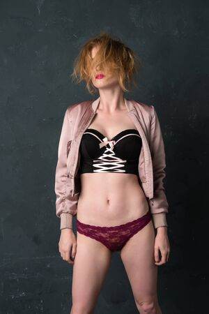 Pretty strawberry blonde woman in a bustier top and jacket