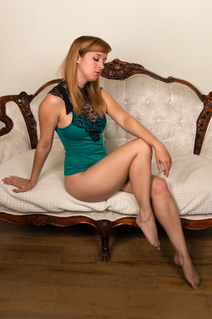 green couch: Pretty young redhead in a blue green bodysuit