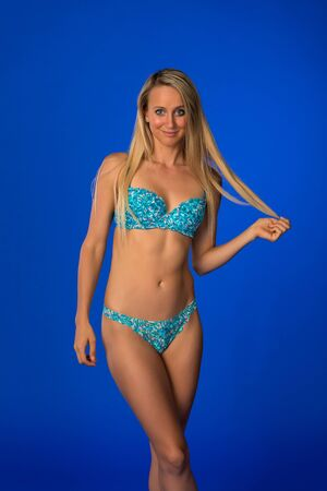 Beautiful slender tanned blonde dressed in blue green lingerie Stock Photo