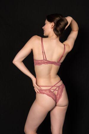 Pretty petite brunette in sheer pink lingerie on black