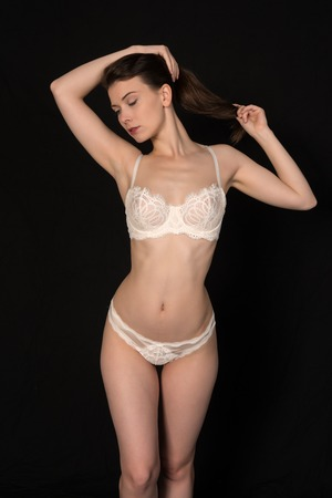 undergarment: Pretty petite brunette in white lingerie on black Stock Photo