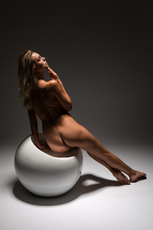 Beautiful petite Czech blonde nude on a white spherical seat Imagens