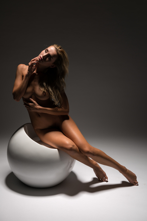 Beautiful petite Czech blonde nude on a white spherical seat 免版税图像