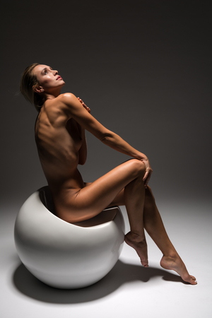 Beautiful petite Czech blonde nude on a white spherical seat Stockfoto