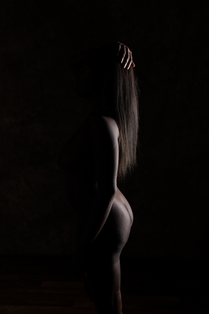 Shapely Ghanaian woman standing nude in deep shadow