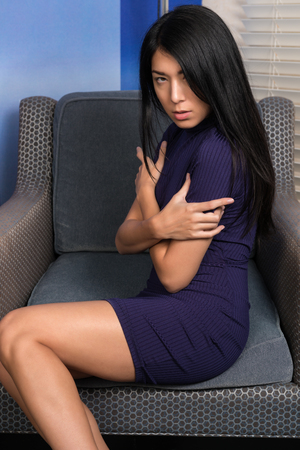 Beautiful petite Eurasian woman in a short purple knit dress