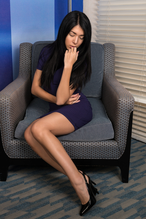 Beautiful petite Eurasian woman in a short purple knit dress