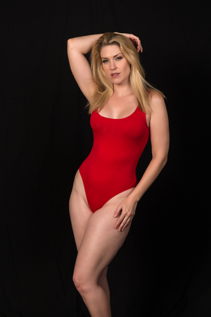 Beautiful pale blonde in a red one piece swimsuit 스톡 콘텐츠