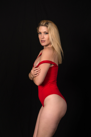 Beautiful pale blonde in a red one piece swimsuit 免版税图像