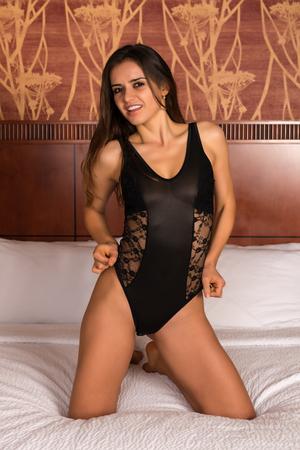 Dark skinned Romanian brunette dressed in a black bodysuit Stock Photo