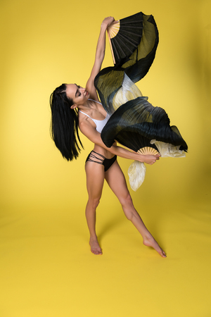 Petite young brunette working with rhythmic gymnastics ribbons Imagens