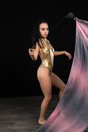 Petite young brunette in a shiny gold leotard