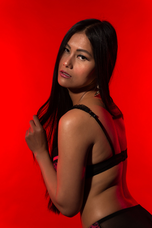 Beautiful petite Filipino woman in red and black lingerie
