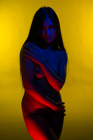 Beautiful petite Filipino woman lit in blue and red