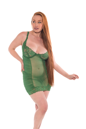 Curvy young redhead in a green lace chemise