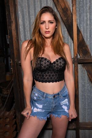 Beautiful brunette in a black bustier top and cutoff denim shorts