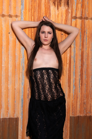 Pretty young brunette standing topless in a black lace dress