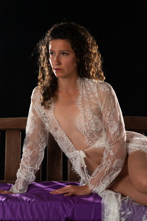 Tall slim brunette in a sheer white lace wrap on a porch swing
