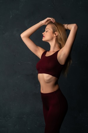Tall slender blonde in a maroon top and slacks