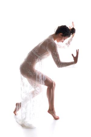 Tall slim brunette dancing in a sheer white lace wrap Standard-Bild