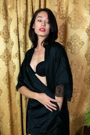 Tall slender Eurasian woman in black lingerie