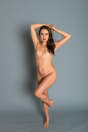 Beautiful petite brunette standing nude on gray Stock Photo