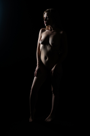 Pretty petite redhead standing nude in deep shadow