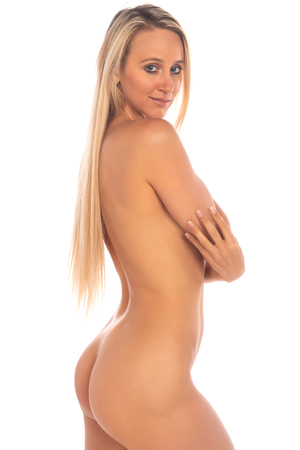 Beautiful slender tanned blonde standing nude on white