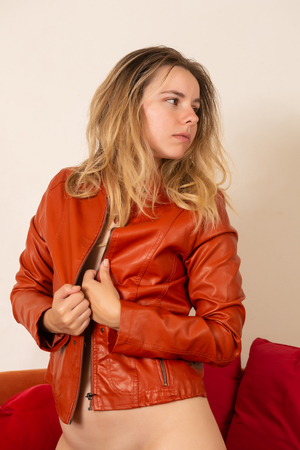 Pretty petite brunette nude under an orange leather jacket Stock fotó