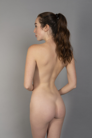 Slender tall young brunette standing nude on gray Stock Photo
