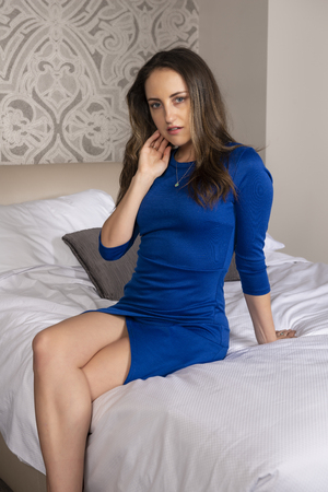 Petite young brunette in a short blue dress