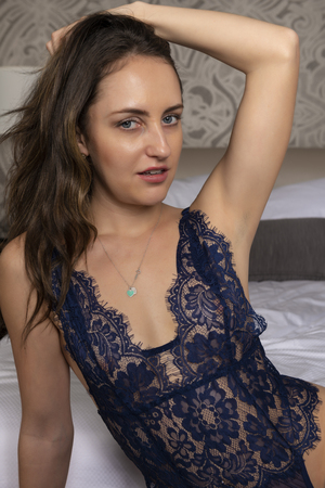Petite young brunette in a blue lace bodysuit