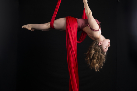 Petite athletic brunette acrobat suspended from red silk Stok Fotoğraf
